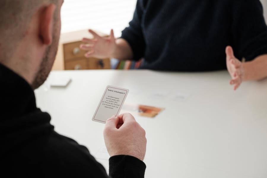 Carola Körner sitzt mit einem jugendlichen Patienten an einem Tisch und spielt ein Rollenspiel mit Karten