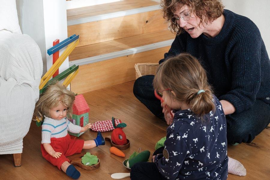 Carola Körner sitzt mit einem Kind auf dem Fußboden und spielt ein Rollenspiel mit einer Puppe und Kochutensilien