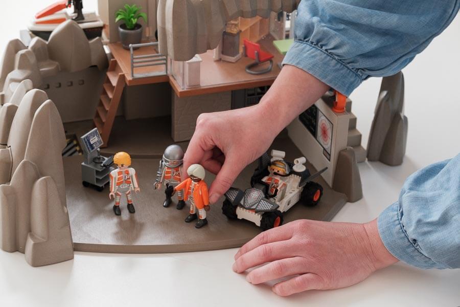 Eine Hand positioniert eine Playmobil-Figur auf einem Spiel, das auf einem Tisch steht