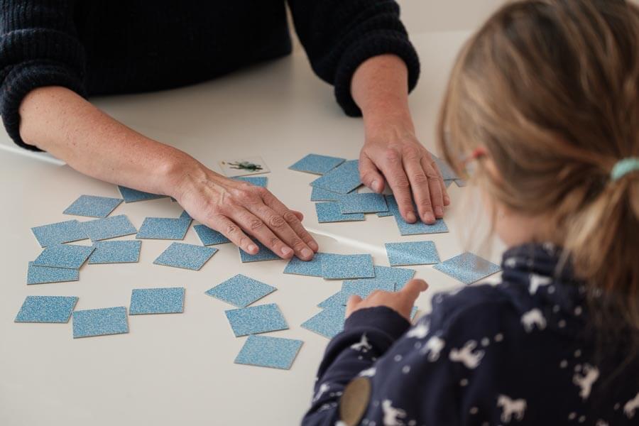 Carola Körner sitzt mit einem Kind an einem Tisch und spielt das Spiel Memory