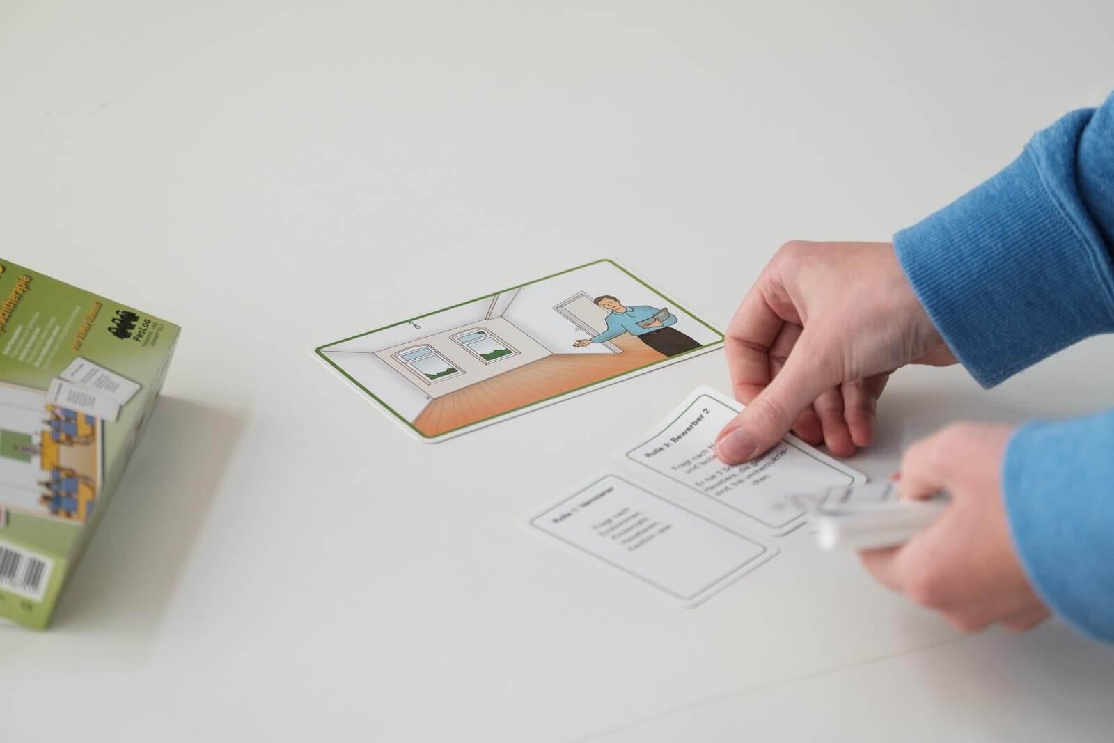 Zwei Hände, die Spielkarten für ein Rollenspiel auf einen weißen Tisch legen